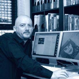 Photo of Kieran Nolan working at his desktop computer